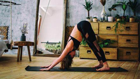 Frau in Yoga Pose Herabschauender Hund